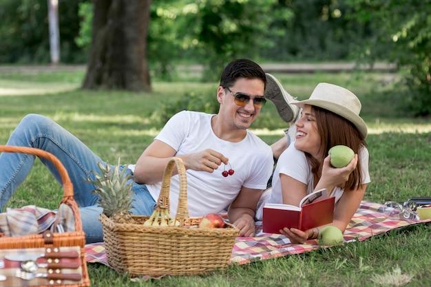 Hombre y mujer comiendo frutas mientras sonríe