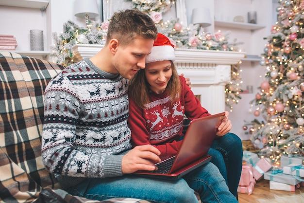 El hombre y la mujer concentrados e interesados trabajan usando la computadora portátil. lo miran. guy presiona los botones. llevan ropa festiva.