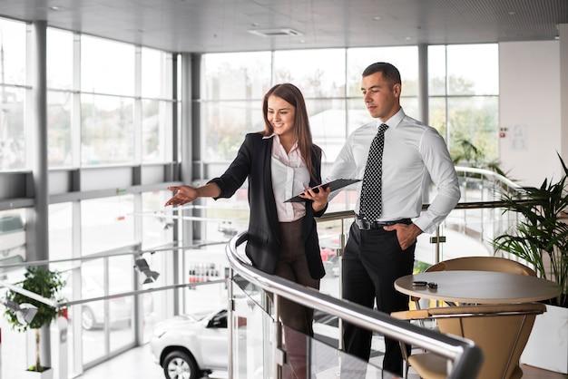 Hombre y mujer en concesionario de automóviles juntos
