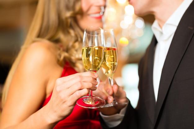 Hombre y mujer con copa de vino espumoso en la mano.