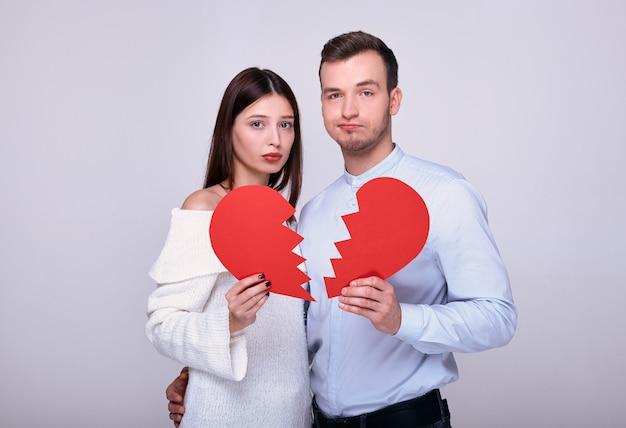 Un hombre y una mujer con un corazón rojo roto.