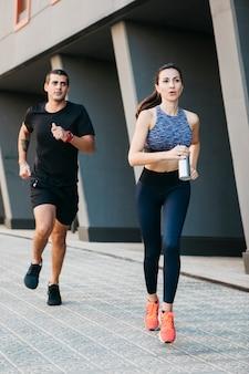 Hombre y mujer corriendo en entorno urbano
