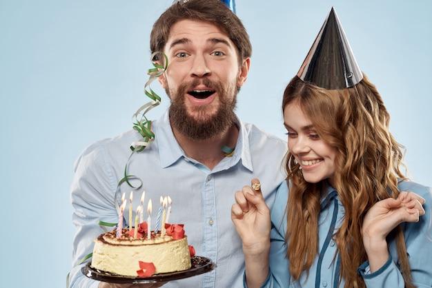 Un hombre y una mujer en un cumpleaños con un pastelito y una vela en un gorro festivo se divierten y celebran la fiesta juntos