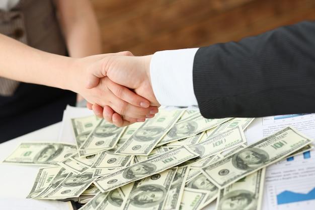 El hombre y la mujer se dan la mano sobre la pila de dólares.