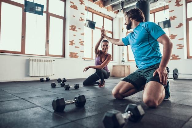 Hombre y mujer dando cinco altos en el club de fitness.