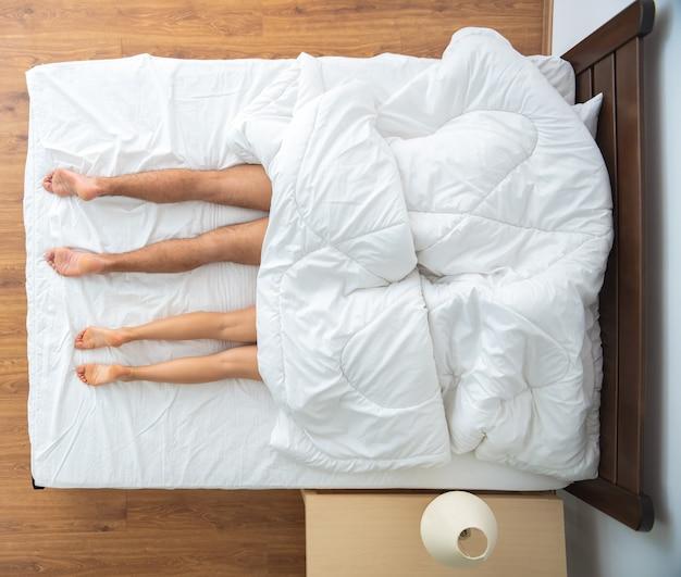 El hombre y la mujer debajo de la manta tendidos en la cama. vista desde arriba