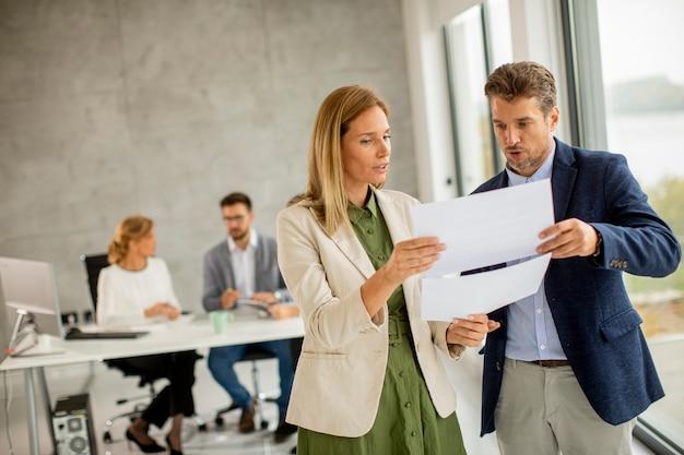 Hombre y mujer discutiendo con papel en las manos en el interior de la oficina con jóvenes trabaja detrás de ellos