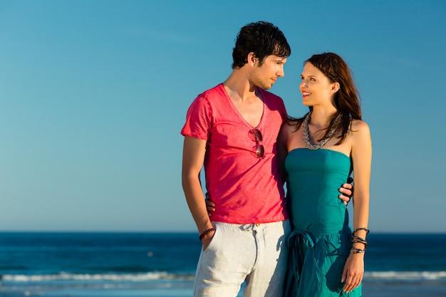 Hombre y mujer disfrutando del atardecer en la playa