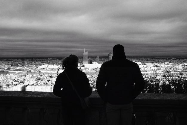 Un hombre y una mujer disfrutando de la vista de la ciudad al atardecer
