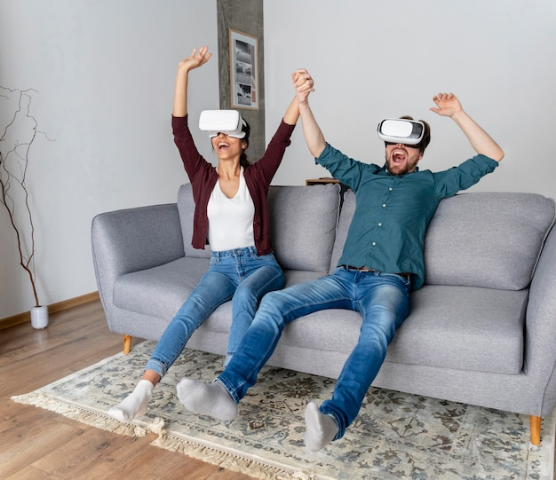 Hombre y mujer divirtiéndose en casa con casco de realidad virtual