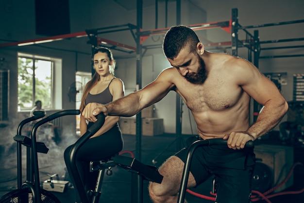 Hombre y mujer durante los ejercicios en el gimnasio.