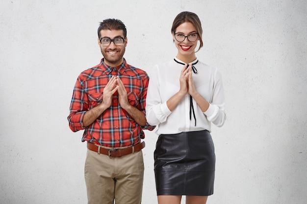El hombre y la mujer elegantes y esperanzados mantienen las palmas juntas mientras esperan algo, tienen expresiones curiosas
