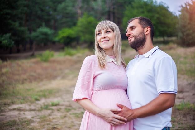 Hombre y mujer embarazada en la naturaleza, en medio del bosque de pinos.