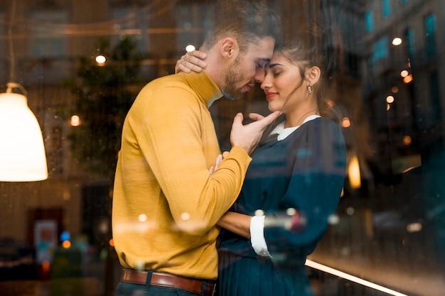 Hombre y mujer encantadora que abrazan en restaurante cerca de la ventana