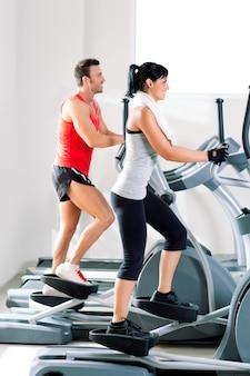 Hombre y mujer con entrenador de cruz elíptica en el gimnasio