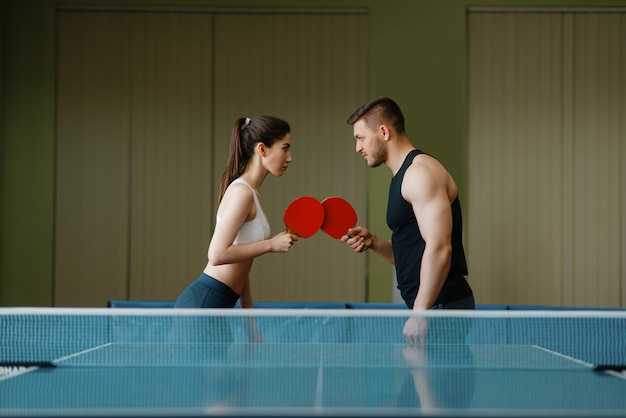 Hombre y mujer en el entrenamiento de ping pong en interiores.