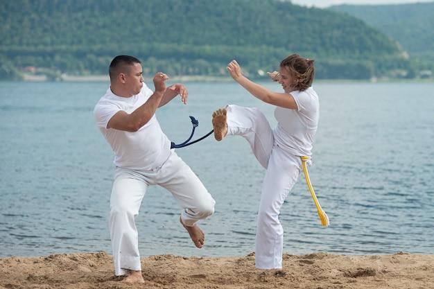 El hombre y la mujer entrenan a la capoeira en la playa - concepto sobre personas, estilo de vida y deporte.