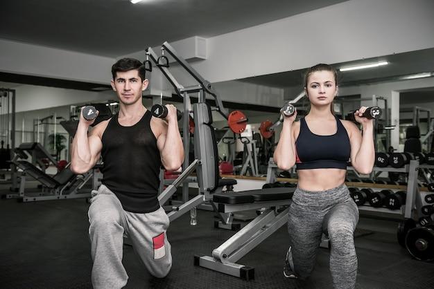 Hombre y mujer entrenando en pareja en el gimnasio