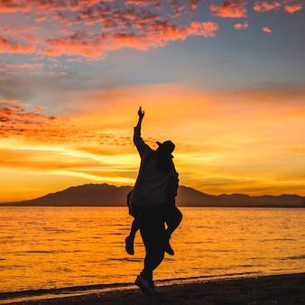 Hombre con mujer en la espalda en la orilla del mar oscuro