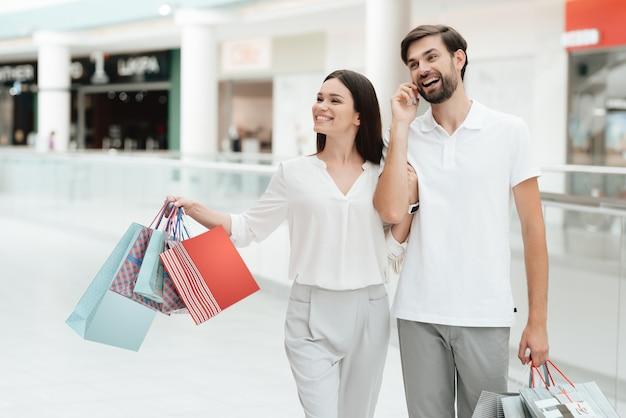 El hombre y la mujer están caminando a otra tienda en centro comercial.