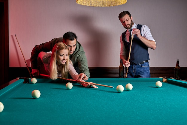 Un hombre y una mujer están jugando al billar, un chico le está enseñando a una mujer a jugar al billar. entretenimiento, concepto de vacaciones