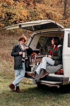 El hombre y la mujer están listos para un viaje por carretera en una furgoneta