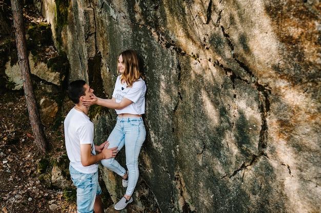 Un hombre y una mujer están parados cerca de una gran roca.