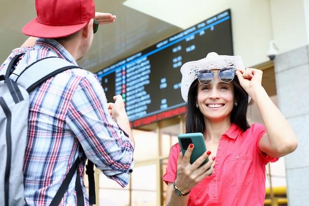 El hombre y la mujer están de pie bajo el tablero de anuncios en la estación de tren