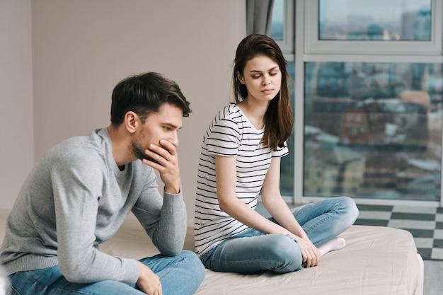 Un hombre y una mujer están sentados en la cama y hablan de una relación, una verdadera disputa.