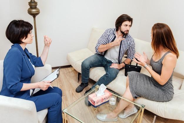 El hombre y la mujer están sentados juntos y mirándose. están discutiendo guy apunta a su esposa. el psicólogo los escucha y analiza su comportamiento.