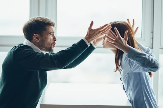 Un hombre y una mujer están sentados en una mesa hablando, discutiendo entre ellos, una verdadera disputa, problemas domésticos