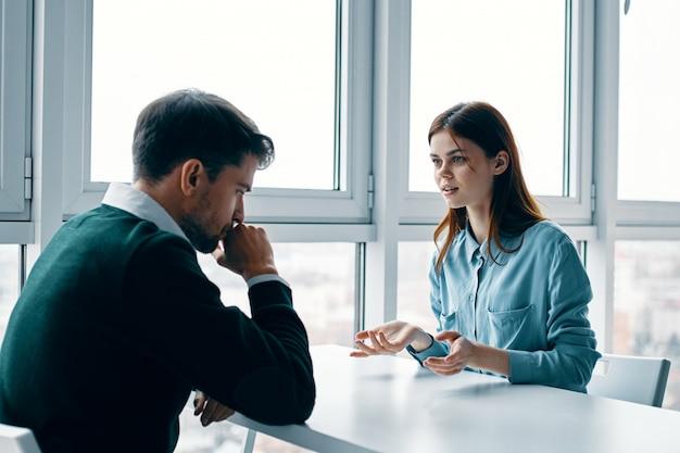 Un hombre y una mujer están sentados en una mesa hablando, discutiendo, una verdadera disputa, problemas domésticos
