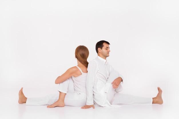 Hombre y mujer están sentados en pose de yoga.