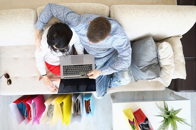 El hombre y la mujer están sentados en el sofá abrazados y comprando en línea