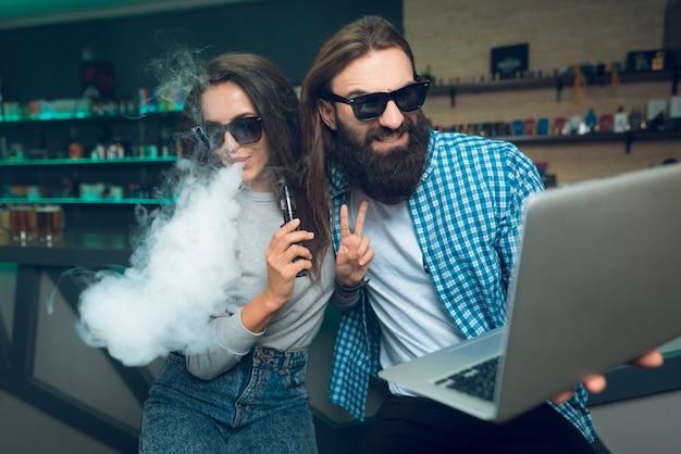 Un hombre y una mujer están sentados con un vaporizador y una computadora portátil.