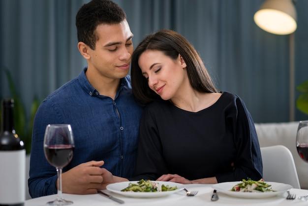 Hombre y mujer estando cerca en su cena romántica