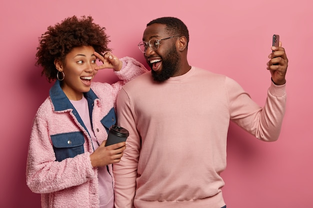 Hombre y mujer étnica divertida toman retrato selfie en celular moderno