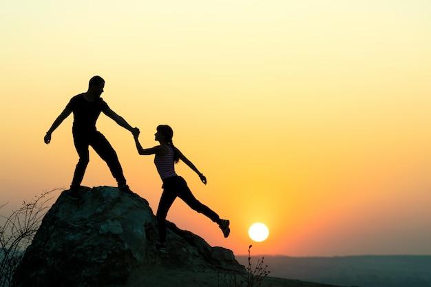 Hombre y mujer excursionistas ayudándose mutuamente a subir una gran piedra al atardecer en las montañas. pareja escalada en una roca alta en la naturaleza de noche. concepto de turismo, viajes y estilo de vida saludable.