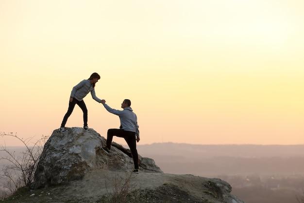 Hombre y mujer excursionistas ayudándose mutuamente a subir piedra al atardecer en las montañas