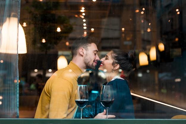Hombre y mujer felices cerca de copas de vino en restaurante