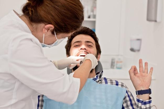 Hombre y mujer felices jovenes en un examen dental en el dentista