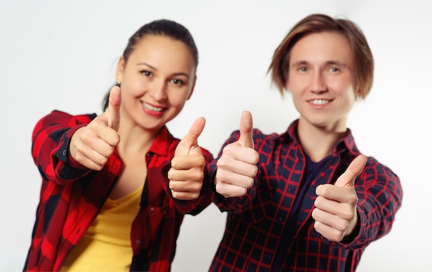 El hombre y la mujer felices jovenes muestran los pulgares encima del gesto. en blanco manos enfocadas, cara desenfocada