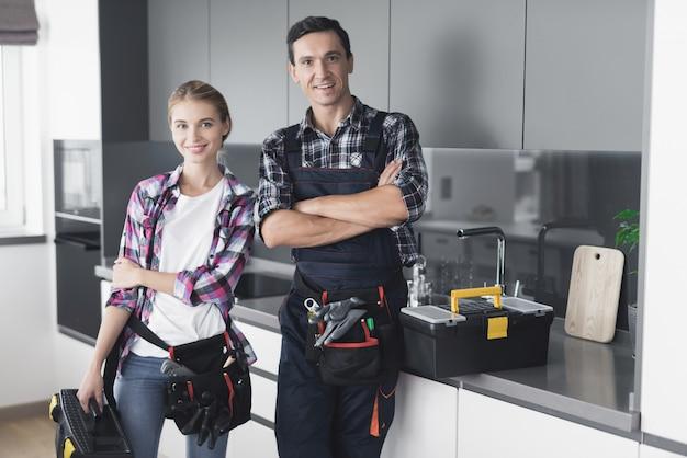 Un hombre y una mujer fontanero están de pie en la cocina.