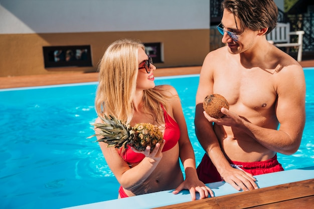 Hombre y mujer con frutas en la piscina