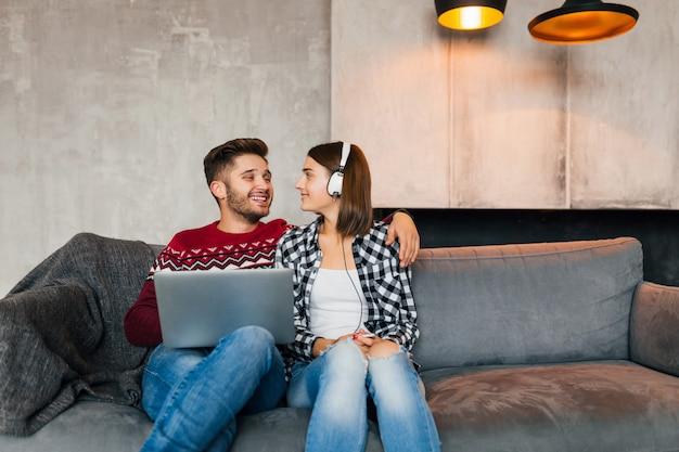 Hombre y mujer guapos jóvenes sentados en casa en invierno mirando en la computadora portátil con expresión de cara de tristeza sorprendida, asustado, viendo una película de terror en una cita, usando internet, pareja en el tiempo libre juntos, citas