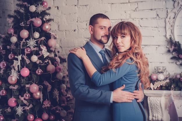Hombre y mujer en habitación con árbol de navidad y chimenea
