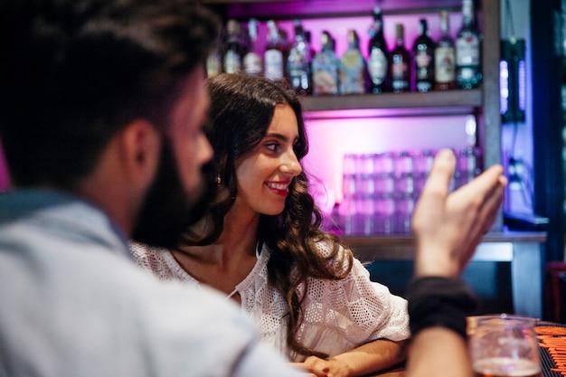 Hombre y mujer hablando en bar elegante
