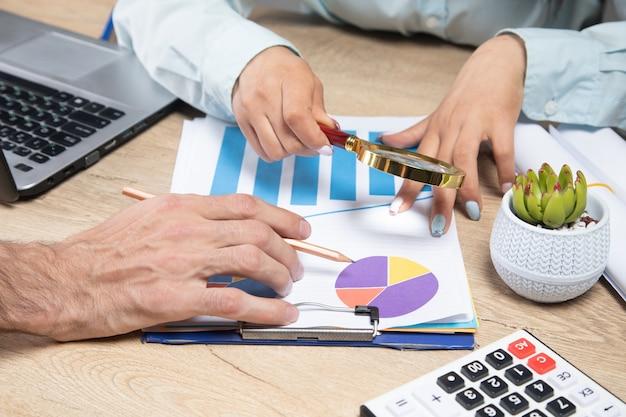 Un hombre y una mujer hablando de estadísticas en su escritorio.