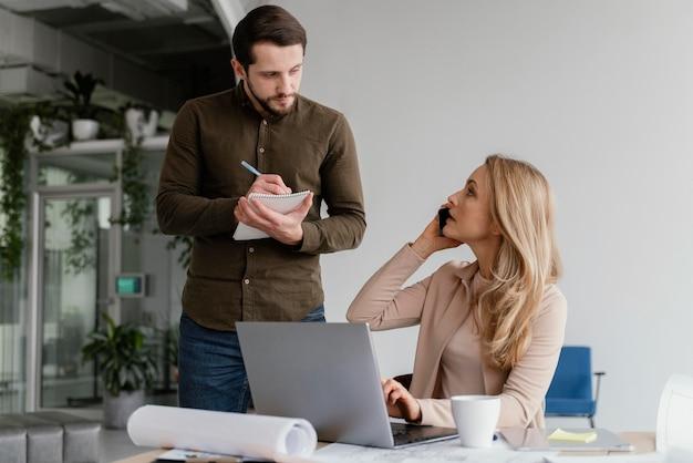 Hombre y mujer hablando de un proyecto en una reunión