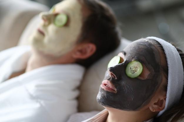 Hombre y mujer hacen mascarilla de arcilla rejuvenecedora para restaurar la piel del rostro